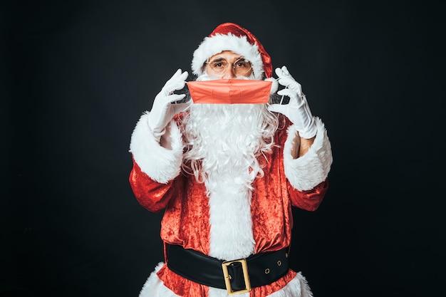 サンタクロースに扮した男が、黒い背景に、感染を防ぐために赤いマスクをかぶっています。クリスマスのコンセプト、サンタクロース、ギフト、お祝い。