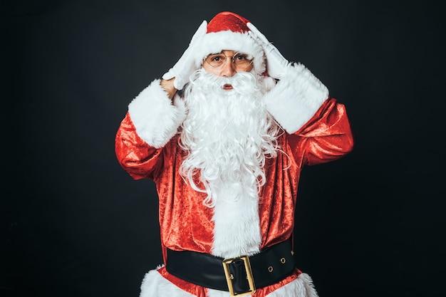 サンタクロースに扮した男が、黒い背景に、頭に手を当てて驚いた。クリスマスのコンセプト、サンタクロース、ギフト、お祝い。