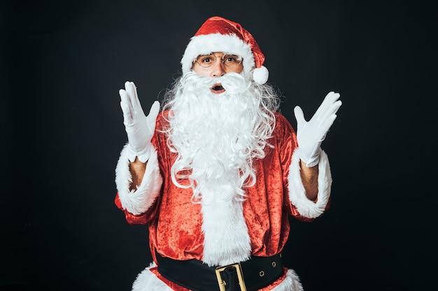 サンタクロースに扮した男が、黒い背景に手を上げて驚いた。クリスマスのコンセプト、サンタクロース、ギフト、お祝い。