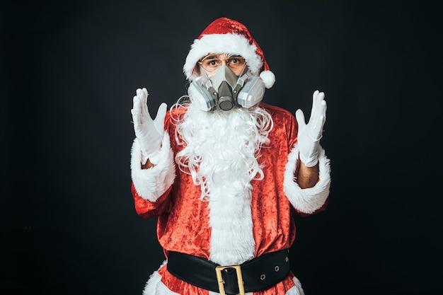 黒の背景に、ウイルスを捕まえるのを避けるためにカーボンフィルターマスクを身に着けているサンタクロースに扮した男。クリスマスのコンセプト、サンタクロース、ギフト、お祝い。