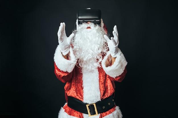 黒の背景に、仮想現実の眼鏡をかけてサンタクロースに扮した男。クリスマスのコンセプト、サンタクロース、ギフト、お祝い。