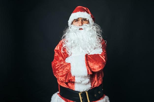 黒の背景に、腕を組んでサンタクロースに扮した男。クリスマスのコンセプト、サンタクロース、ギフト、お祝い。