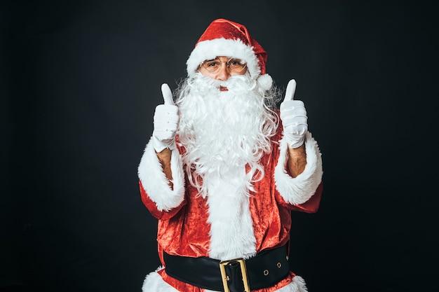 黒の背景に、親指を立ててサンタクロースに扮した男。クリスマスのコンセプト、サンタクロース、ギフト、お祝い。