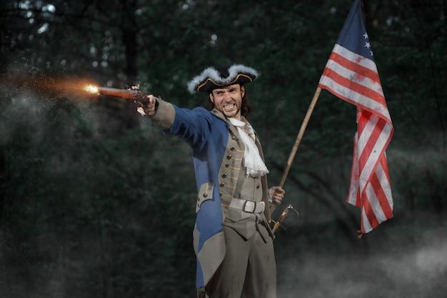 アメリカのアメリカ革命戦争の兵士に扮した男はフラグ付きのピストルから目指しています