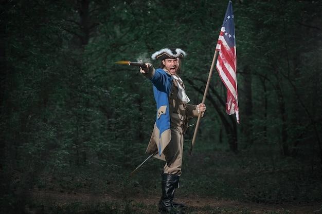 ピストルとフラグを持つアメリカのアメリカ独立戦争の兵士に扮した男