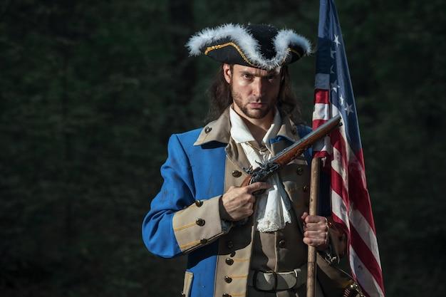アメリカ独立戦争の兵士に扮した男が旗を掲げたピストルを狙う