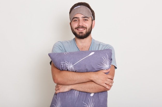 Man dressed gray casual t shirt ready to go to bed, white wall on. guy with happy face holds pillow. macho with beard and mustache relaxing, having nap, resting at home