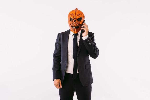 정장 재킷, 파란색 넥타이, 잭오랜턴 호박 마스크를 입은 남자가 미친 듯이 휴대전화로 통화합니다. 할로윈과 카니발 축하 개념입니다.