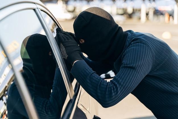 검은 옷을 입은 남자가 머리에 발라클라바를 하고 훔치기 전에 차 유리를 바라보고 있다. 자동차 도둑, 자동차 절도 개념