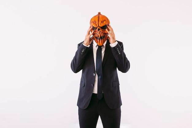 재킷 정장, 파란색 넥타이, 잭오랜턴 호박 마스크를 입은 남자가 미친 듯이 머리에 손을 얹고 있습니다. 할로윈과 카니발 축하 개념입니다.