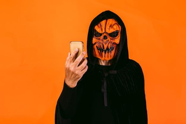 カボチャのラテックスマスクとフード付きのベルベットのマントを着た男が携帯電話を見ています。ハロウィーンと死んだコンセプトの日々。