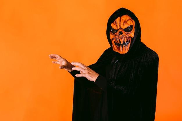 カボチャのラテックスマスクとフード付きのベルベットのマントに身を包んだ男は、オレンジ色の背景に、彼の手で怖がります。ハロウィーンと死んだコンセプトの日々。