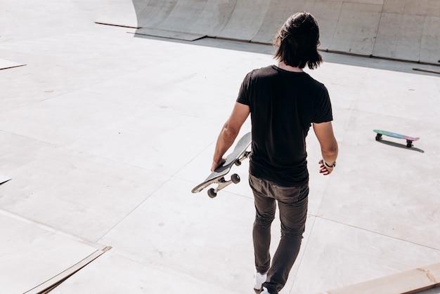 손에 스케이트보드를 들고 평상복을 입은 남자가 화창한 날 밖에 있는 스케이트 공원의 미끄럼틀을 걷고 있습니다.