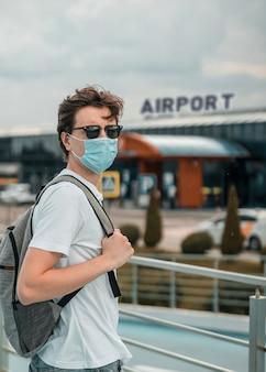남자는 흰색 티셔츠, 청바지 반바지, 선글라스, 수술 용 마스크와 배낭을 다시 입고. 백그라운드에서 공항
