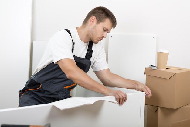 Мужчина в комбинезоне рабочих собирает мебель. сделай сам, дом и концепция перемещения