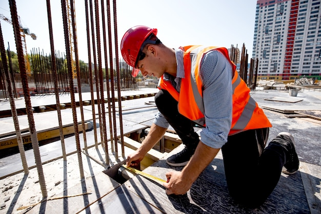 Man dressed in shirt, orange work vest and helmet measures the hole with a tape measure on the building site .