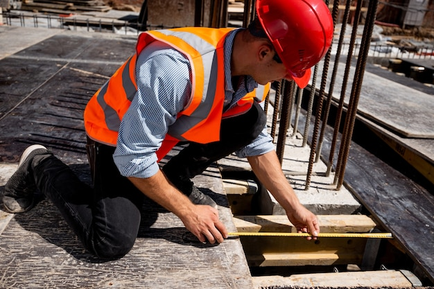 Man dressed in shirt, orange work vest and helmet measures the hole with a tape measure on the building site . .