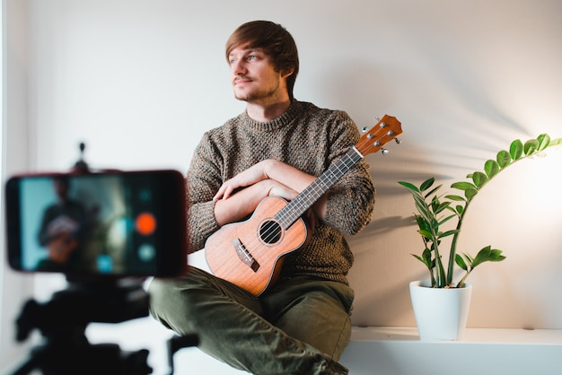 Man dressed in a sweater takes off the vlog of a game on a ukulele at home on the phone.