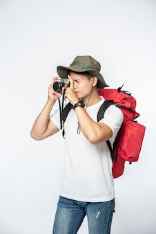 A man dressed to travel wearing a hat and taking a camera