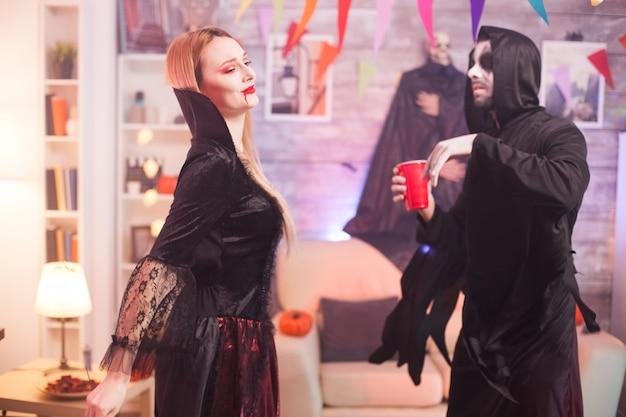男はハロウィーンのお祝いで美しい吸血鬼の女性と踊る死神のようにドレスアップしました。