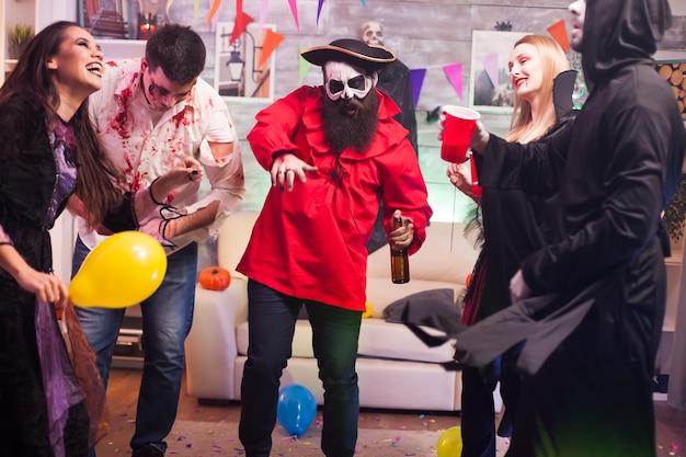 Человек, одетый как пират, танцует вокруг своих друзей, празднующих хэллоуин.