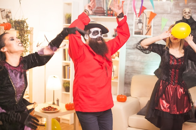 男はハロウィーンを祝っている間、手を上げて踊るひげを生やした海賊のようにドレスアップしました。