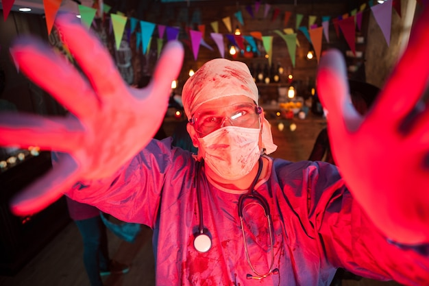 Man dressed up like a doctor having fun at a halloween party. halloween party in a night club.