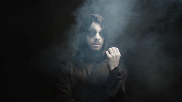 Man dressed up like grim reaper for halloween party over a black background with smoke