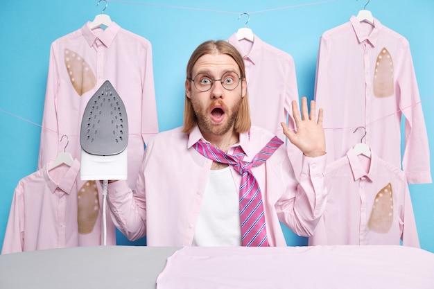 L'uomo si veste per un appuntamento o una riunione aziendale stira i vestiti con il ferro da stiro elettrico sull'asse da stiro impegnato a fare le faccende domestiche