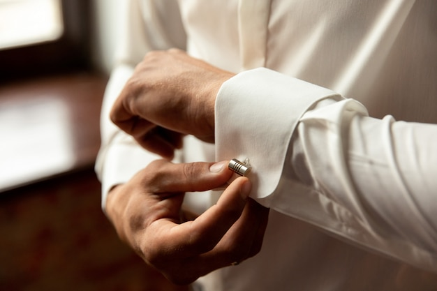 Man dressing up and adjusting white shirt with cufflinks