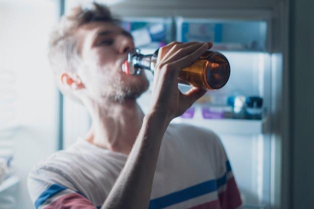 Человек пьет медведя из холодильника в ночное время b