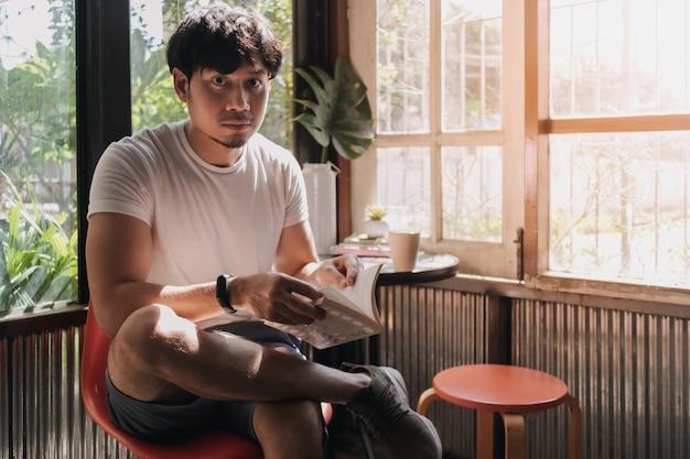 男は暖かい光の夏にコーヒーを飲み、本を読む