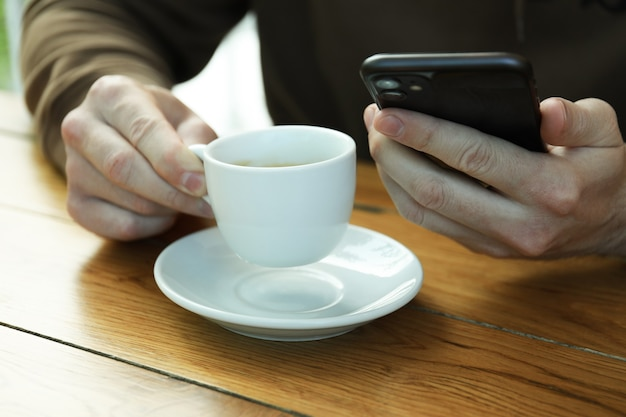 Man drink coffee and holds phone, close up