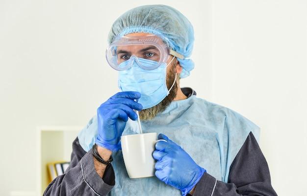 남자는 인공 호흡기 보호 마스크에 커피를 마신다. 코로나바이러스 전염병 발생. 의사 호흡 호흡 마스크입니다. 병원이나 오염은 안면 마스킹을 보호합니다. 코로나 보호용 의료 마스크.