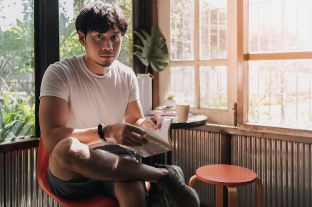 Man drink coffee and reading book in warm light summer
