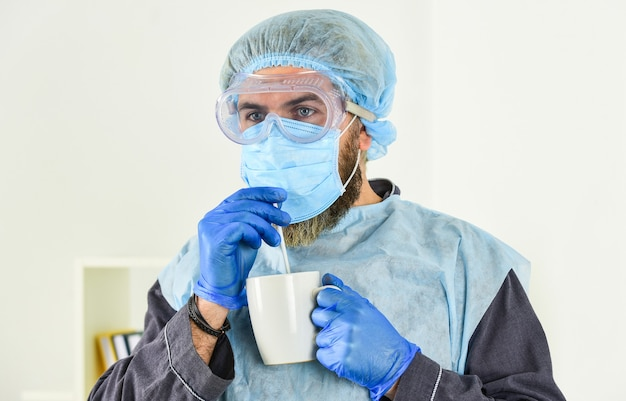 Man drink coffee in respirator protective mask. coronavirus pandemic outbreak. doctor breathing respiratory mask. hospital or pollution protect face masking. medical mask as corona protection.