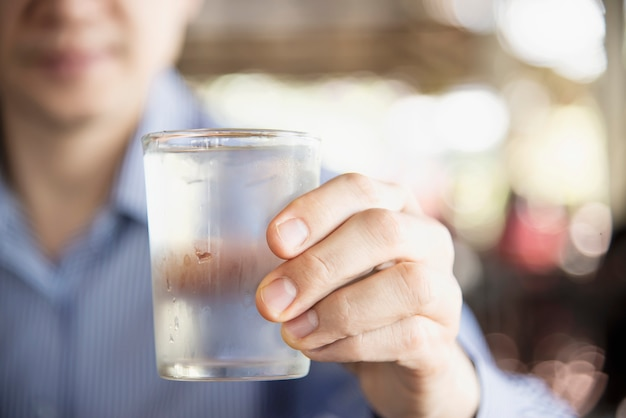 Man drink fresh cold pure water in glass