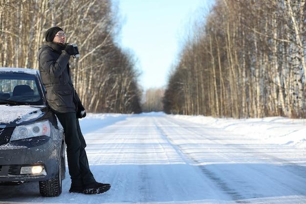 남자는 겨울 화창한 날 야외 머그에서 뜨거운 차를 마신다