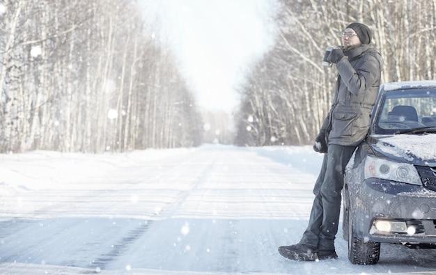 男は冬の晴れた日に屋外のマグカップから熱いお茶を飲みます