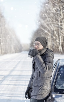 男は冬の道路で屋外のマグカップから熱いお茶を飲む