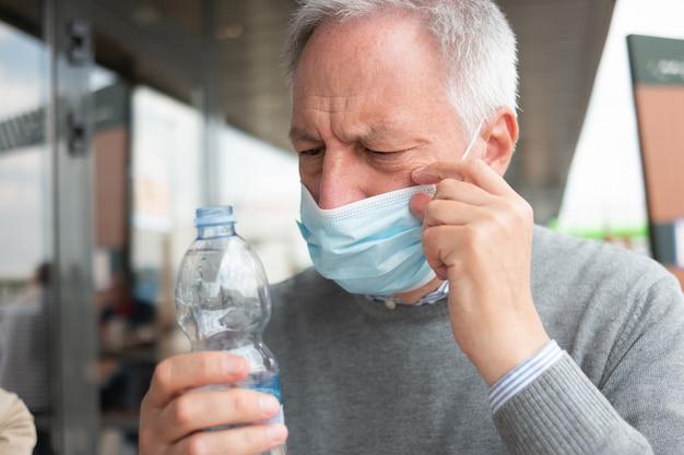 コロナウイルスのパンデミック時に水のボトルを飲む男性
