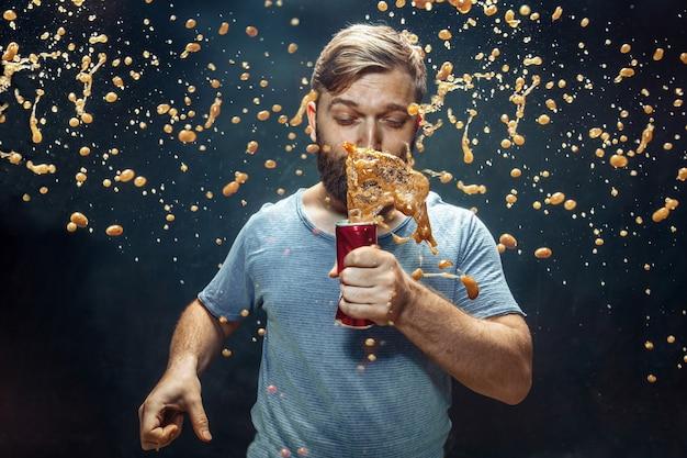 Мужчина пьет колу в студии. молодой улыбающийся счастливый кавказский парень, открывающий банку с колой и наслаждающийся спреем. рекламное изображение любимого напитка. концепция образа жизни и человеческих эмоций.