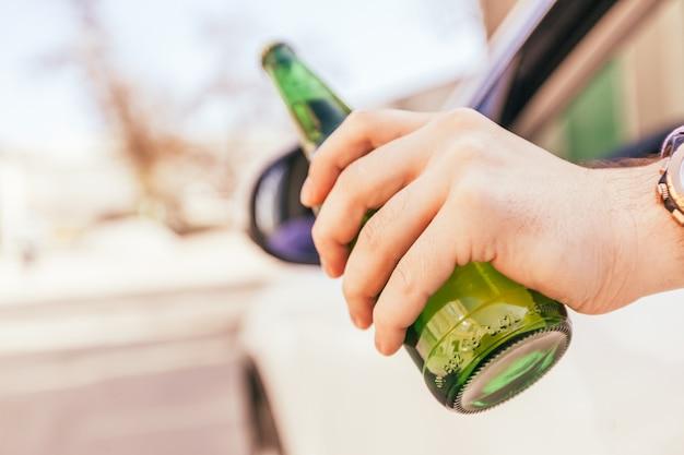 車の運転中にアルコールを飲む男