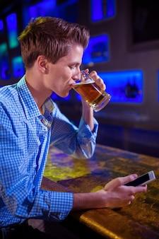 バーのカウンターでビールを飲む男性