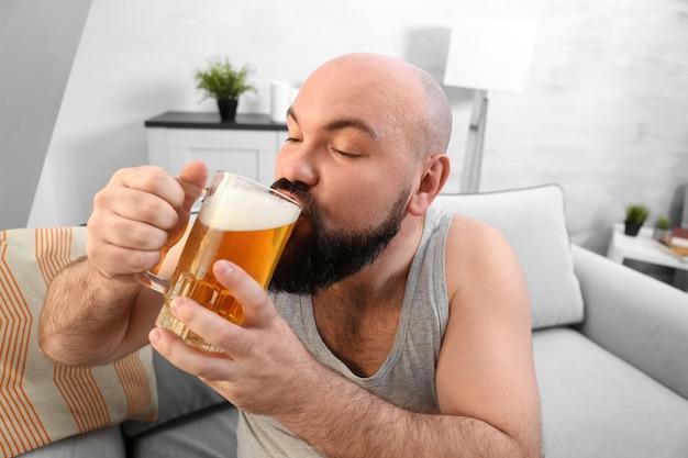 家でビールを飲む男
