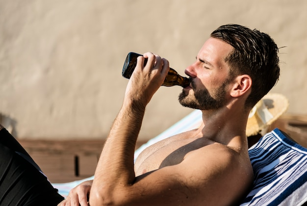 Man drinking a beer by the pool