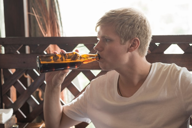 Man drinking beer from bottle in bar