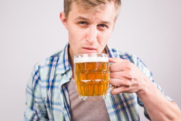 맥주를 마시는 남자. 맥주 잔을 들고 행복 한 젊은 남자.