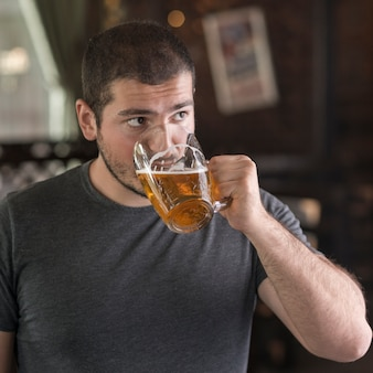 Man drinking beer and looking away