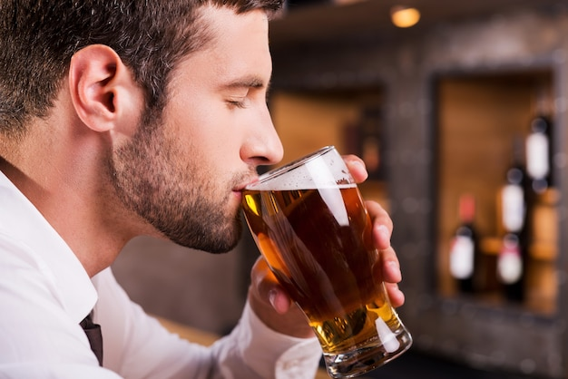 Мужчина пьет пиво. вид сбоку красивого молодого человека, пьющего пиво, сидя за барной стойкой